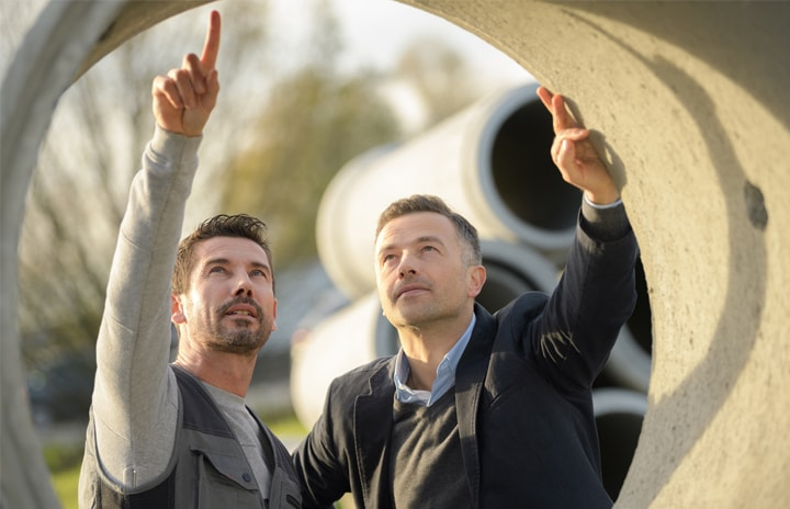 Two men looking at a concrete pipe
